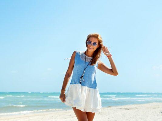 adolescente-com-oculos-de-sol-e-vestido-azul-na-praia_1140-97