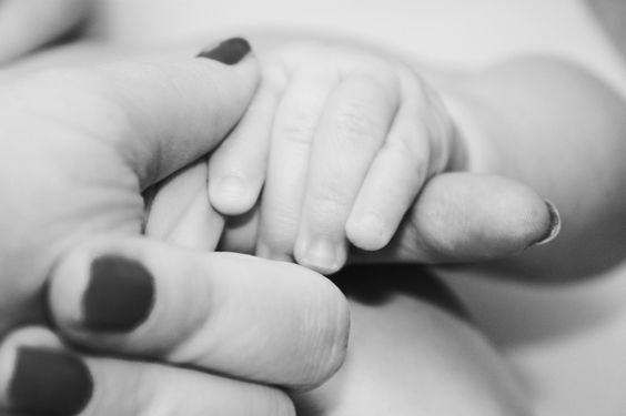 mae segurando a mao do bebê